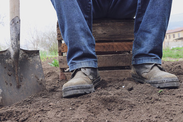 A man with a shovel in the garden rest after sowing