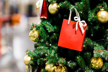 Image of Christmas tree with gold balls, red packet for gifts