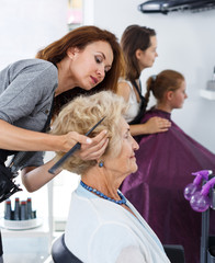 Stylist doing hairdress for senior lady
