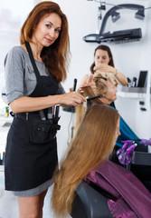 Hairdresser doing styling of girl