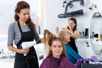 Hairdresser drying hair of teen girl