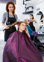 Teen girl in barber chair with phone