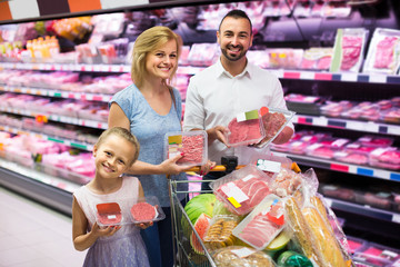 parents with daughter choosing meat in refrigerated section in hypermarket