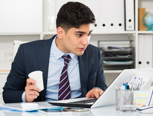 Businessman is working at a computer and drinking coffee