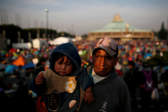 A pilgrim wears a hat with the image of the Virgin of Guadalupe as he carries a child at the Basilica of Guadalupe, during the annual pilgrimage in honour of the Virgin of Guadalupe, patron saint of Mexican Catholics, in Mexico City