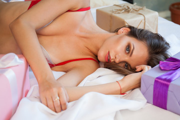beautiful woman in lingerie lying on a bed with gifts holiday