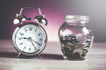 clock with coins on jar
