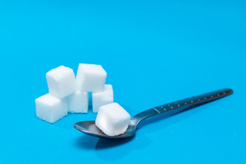 Background of sugar cubes in spoon. White sugar on blue background. Sugar with copy space