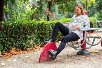 Pregnant attractive woman sitting on playground