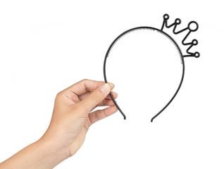 Hand holding Ladies Mini Black Plastic Crown Headband isolated on white background