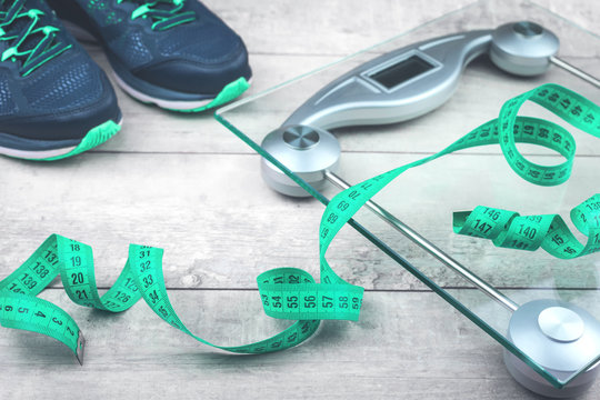 Green measure tape, glass weighing scale, running shoes on a rustic surface. Weight management and healthy wellbeing concept