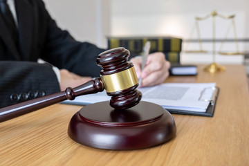 Legal law, advice and justice concept, male lawyer or notary working on a documents and report of the important case and wooden gavel, balance on table in courtroom