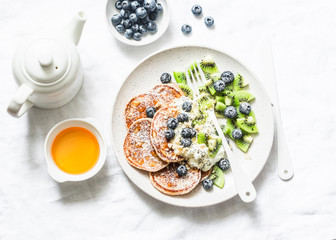 Healthy breakfast or dessert - whole wheat pancakes with greek yogurt, blueberries, kiwi, honey and nuts on a light background, top view. Flat lay