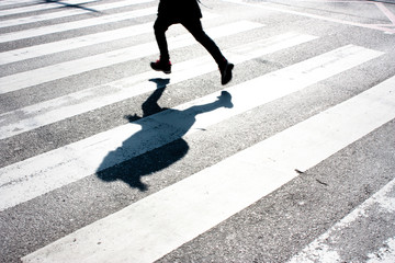 Fotomurales - Blurry child and its shadow on zebra crossing