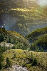 3 mountain bikers riding in a massive Alpine mountain range