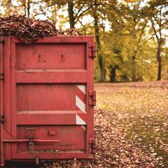 roter Container mit alten Blättern im Park
