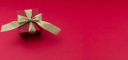 Red gift box with gold ribbon on red background, view from above, copy space