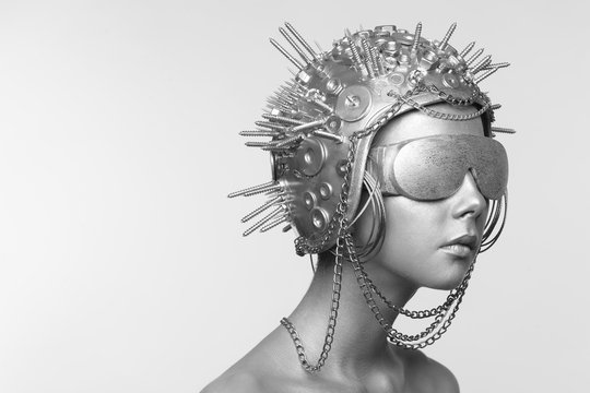 Futuristic woman in metal helmet and glasses