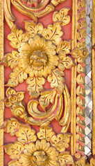 Pattern of gold flower carved on stucco design of native wall, Thai style in temple