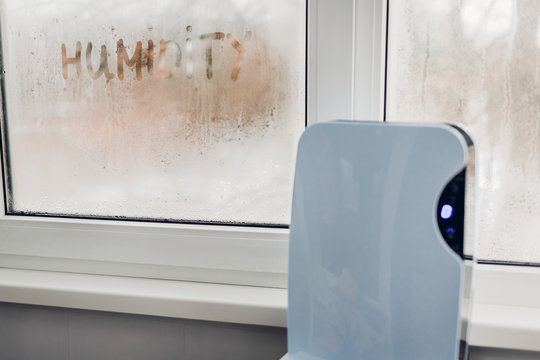 Dehumidifier with touch panel works by wet window in flat. Humidity written on window. Dampness concept.
