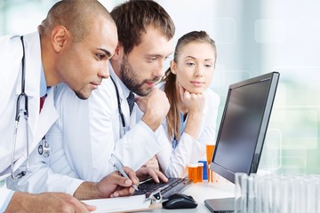 Doctors team talking expertise in hospital by laptop