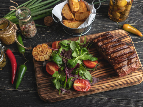 Grilled steak on the board served with herbs, fried potatoes, spices on a black surface