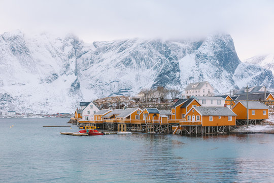 Small town surrounded by snow covered mountains and a river