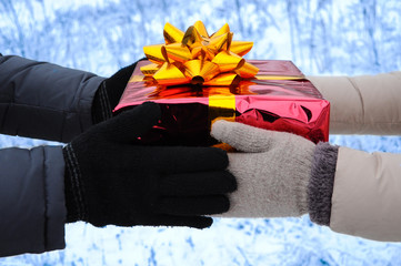 The hands of a man and a woman in winter mittens, exchange wrapped Christmas gift. happy new year. blurred background
