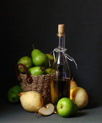 still life-a bottle of wine, wicker basket, whole pears and a half on a dark background