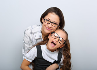 Happy young mother and lauging kid in fashion glasses hugging on empty copy space