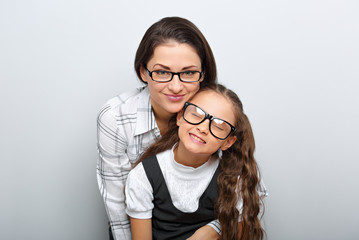 Happy young mother and lauging kid in fashion glasses hugging on empty copy space background. Family portrait