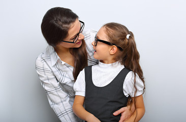 Happy young mother and lauging kid in fashion glasses hugging and looking each other on empty copy space blue background.