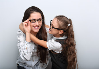 Happy surprising mother and excite kid in fashion glasses looking each other and cuddling on empty copy space background.