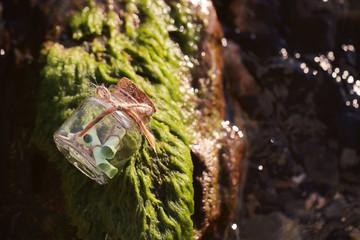 около моря лежит стеклянная прозрачная банка с посланием