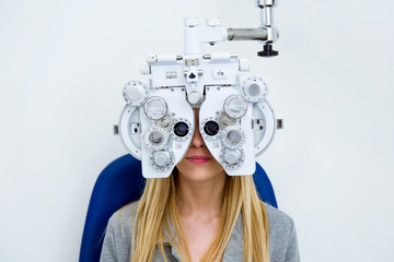 Pretty young woman doing eyesight measurement with optical phoropter in ophthalmology clinic.