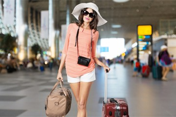 Young woman with travel bag on background