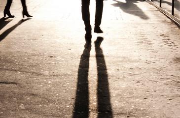 Fotomurales - Defocused shadow and silhouette of legs on city sidewalk