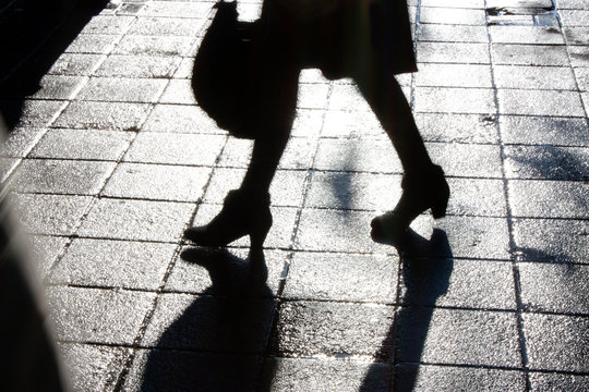 Blurry legs of young woman walking