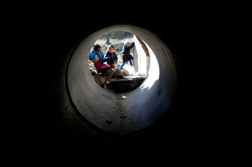 Migrants from Honduras, part of a caravan of thousands from Central America trying to reach the United States, look on as their father walks through a sewage water tunnel to cross the border fence illegally from Mexico to the U.S, in Tijuana