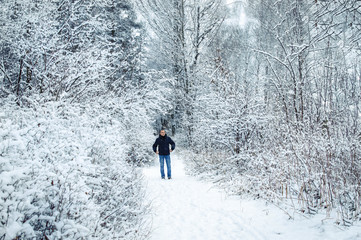 man on a winter day on the background of snowy trees of the forest