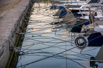 Landscape view of boats tied to shore with many ropes hanging above sea. Sky reflection on the sea. Croatia.