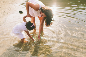 A mother and little girl playing in the water at the beach