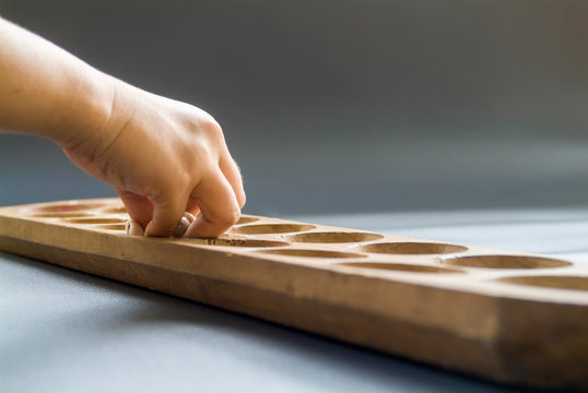 the hand of girl is playing Indonesian traditional mancala games