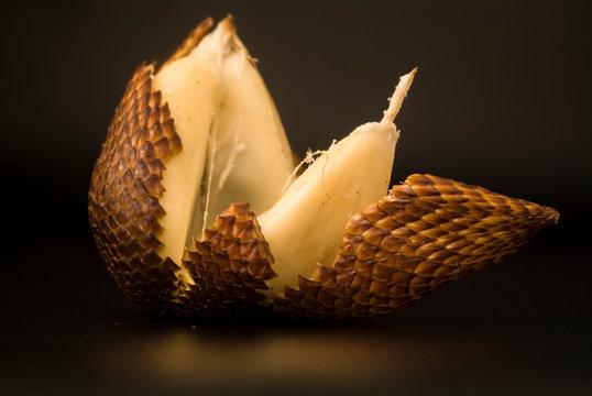 Snakefruit peeled in a black background