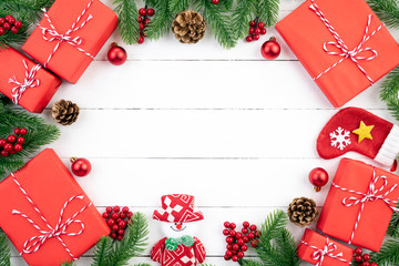 Christmas background concept. Top view of Christmas red gift box with spruce branches, pine cones, red berries and bell on white wooden background.