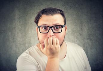 Anxious young man biting nails