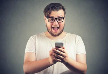 Amazed man with phone reading news