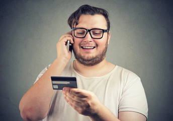 Happy man with card having phone call
