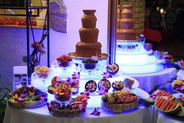 Płynna czekolada na szwedzkim stole, pięknie udekorowane saładki z owoców.