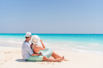 Young couple on white beach during summer vacation. Happy lovers enjoy their honeymoon